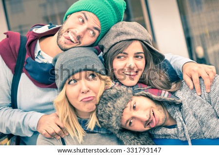Group of best friends taking selfie outdoors with funny face expression and fashion clothes - Happy friendship concept with young hipster people having fun together - Vintage desaturated filtered look - stock photo