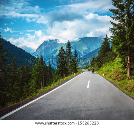 Group of bikers riding on road pass along Alpine mountains, travelers in Europe, mountainous highway, pine tree forest, extreme sport concept - stock photo