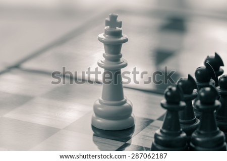 group of black chess on a chessboard and a white king in front of them - stock photo