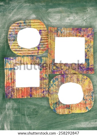 Group of blank colorful painted cardboard frames on grunge chalkboard  - stock photo