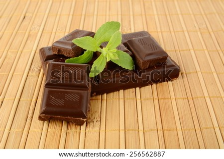 Group of blocks of chocolate with leaves of sage on wooden mat - stock photo