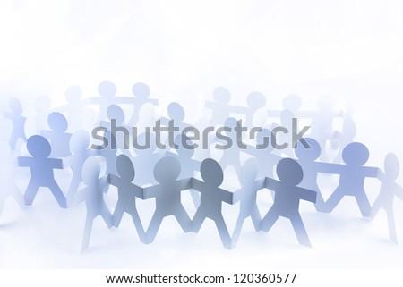 Group of blue paper doll people holding hands on plain background - stock photo
