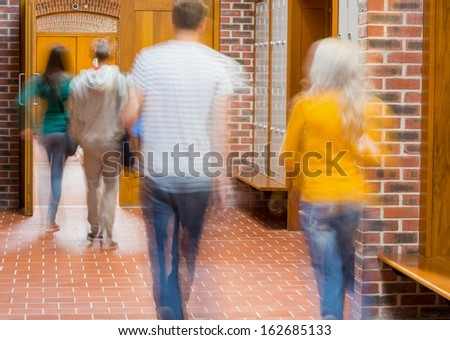 Group of blurred college students walking through corridor - stock photo