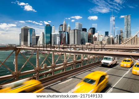 Group of blurred typical yellow New York cabs crossing the Brooklyn Bridge with the Manhattan skyline with blue sky with few clouds  in the background - stock photo