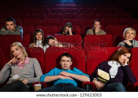 Group of boring people watching movie in cinema - stock photo