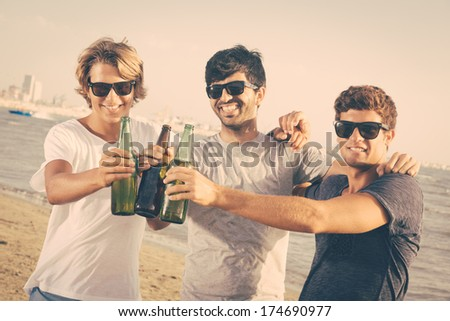 Group of Boys Cheering at Beach - stock photo