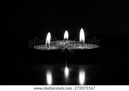 Group of burning candles on  black background. Black and white - stock photo