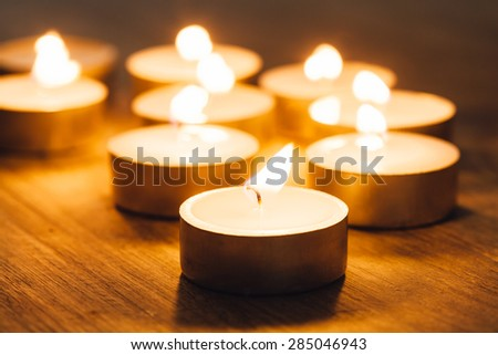 Group of burning candles spa, with focus on a flame - stock photo