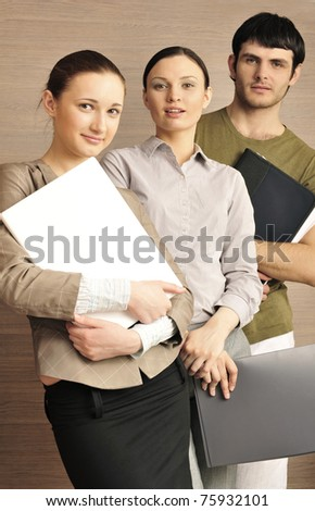 Group of business associates standing together against modern wooden wall at their office one woman holding laptop, man and other woman holding folder with papers and documents. Young entrepreneurs. - stock photo