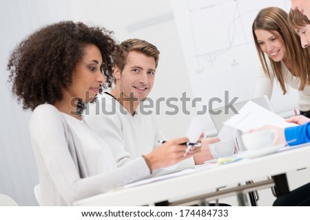 Group of business colleagues in a meeting sitting at a table discussing paperwork with focus to a smiling handsome young man at the back - stock photo