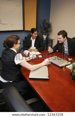 Group of business colleagues sitting in a conference room and playing cards instead of working - stock photo