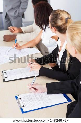 Group of business executives taking notes during a meeting at office - stock photo