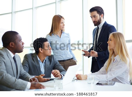 Group of business partners discussing ideas at meeting in office - stock photo