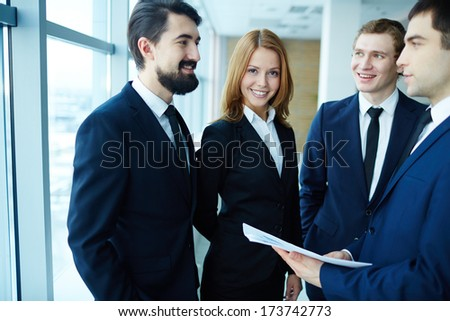 Group of business partners discussing paper and explaining ideas at meeting, happy woman looking at camera - stock photo