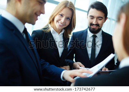 Group of business partners discussing papers and explaining ideas at meeting with focus on happy woman looking at camera - stock photo