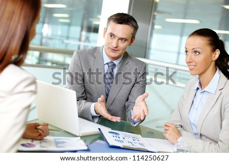 Group of business partners interacting at meeting in office - stock photo