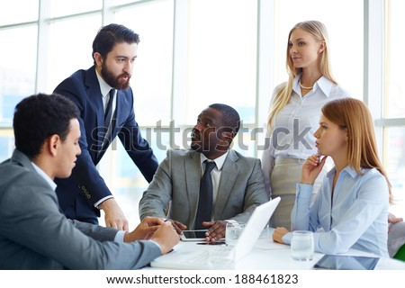 Group of business partners listening to their boss at meeting in office - stock photo