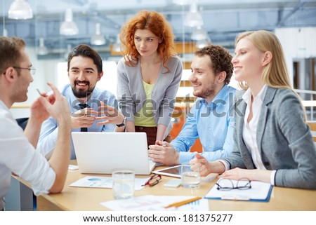 Group of business partners listening to their colleague explanations at meeting - stock photo