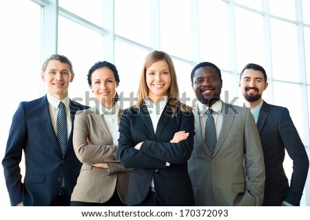 Group of business partners looking at camera with smiles, pretty leader in front - stock photo