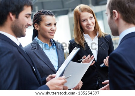 Group of business partners looking at their colleague during negotiations - stock photo