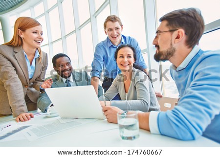 Group of business partners looking at their colleague while he sharing his ideas at meeting - stock photo