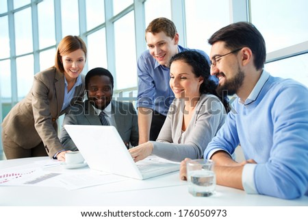 Group of business partners looking with smiles at laptop display at meeting - stock photo