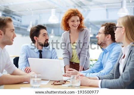 Group of business partners sharing ideas upon computer project at meeting - stock photo
