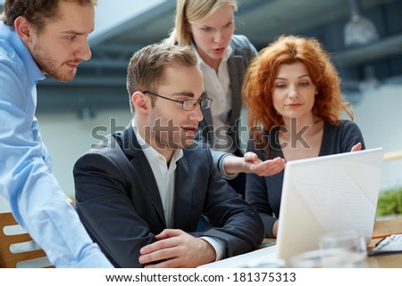 Group of business partners working with laptop at meeting - stock photo