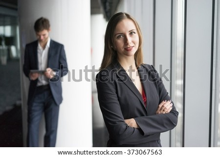 Group of business people, a woman in jacket and man in a suit, winter city landscape outside the window on the background - stock photo