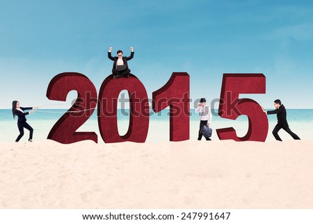 Group of business people arrange number 2015 on beach - stock photo