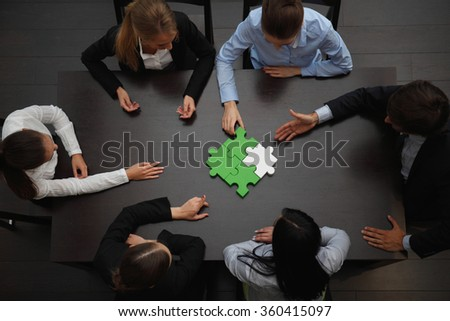 Group of business people assembling jigsaw puzzle, team support and help concept - stock photo