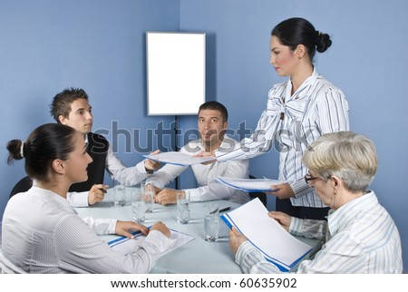 Group of  business people at meeting table sitting on chair while a business young woman giving all folders with papers - stock photo