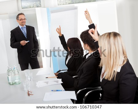 Group of business people at presentation raising hands in the office - stock photo