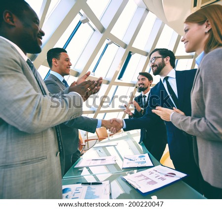 Group of business people clapping their hands while their colleagues handshaking - stock photo