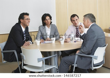 Group of business people having a discussion at conference table - stock photo