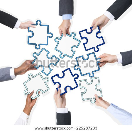 Group Of Business People Holding Pieces Of Puzzle  - stock photo