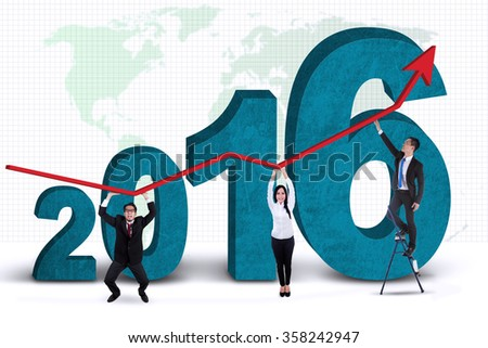 Group of business people holding upward arrow with numbers 2016 and world map background - stock photo