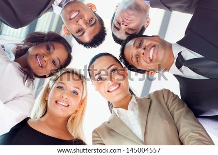 group of business people in a circle looking down - stock photo