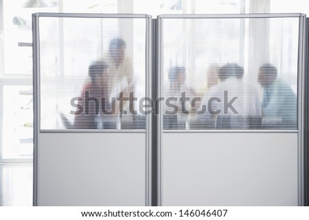 Group of business people in meeting behind translucent wall in office - stock photo