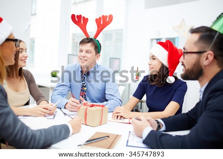Group of business people in Santa caps and with deer horns interacting at meeting on Christmas day - stock photo
