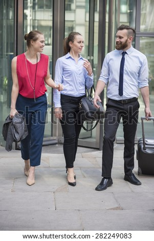 Group of business people leaving office building - stock photo