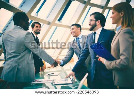 Group of business people looking at their colleagues handshaking in office - stock photo