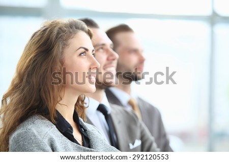 Group of business people looking upwards and smiling - stock photo