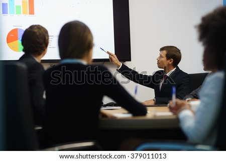 Group of business people meeting in corporate conference room, smiling during a presentation. The coworkers are examining charts and slides on a big TV monitor - stock photo