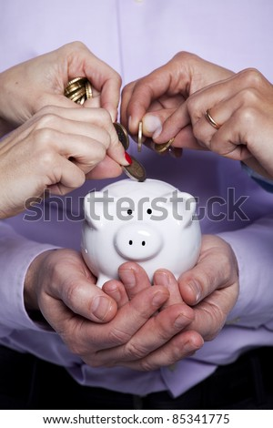 Group of business people saving money on the piggy bank - stock photo