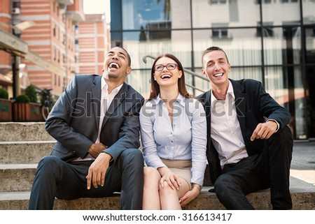 Group of business people sitting on stairs laughing. Shallow depth of field. - stock photo