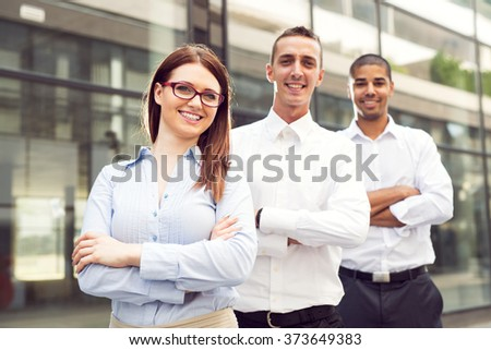 Group of business people standing in front of their office. - stock photo