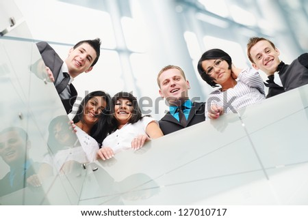 Group of business people standing inside the modern glass building - stock photo