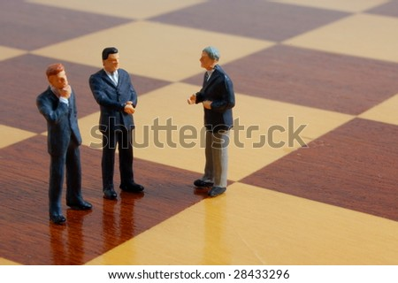 group of business people standing on a chess board - stock photo