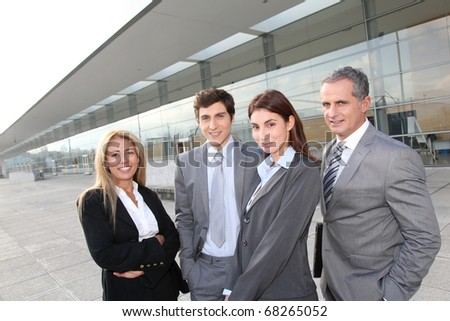 Group of business people standing outside building - stock photo